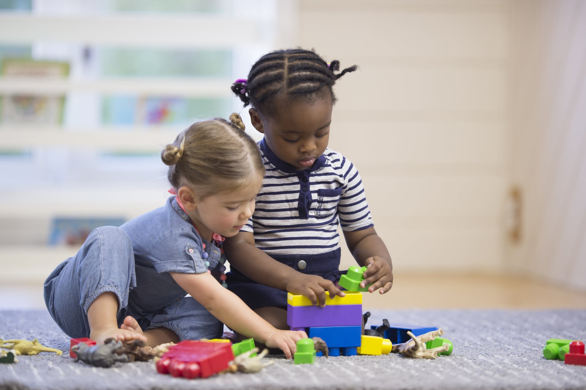 A multi-ethnic group of preschoolers are playing with plastic blocks together in class.