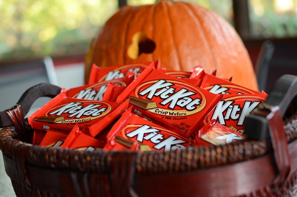 A basket overflowing with Kit-Kat bars sit in front of a partially visibly Jack-o-lantern