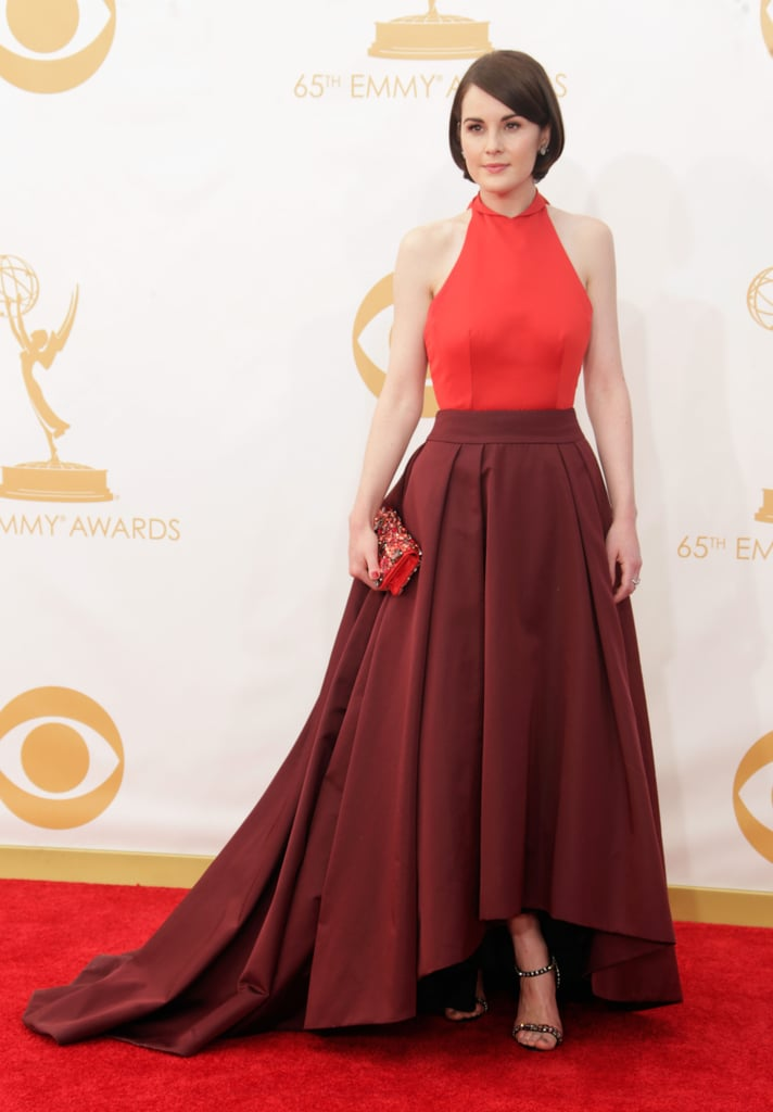 Michelle Dockery went with a two-tone Prada gown for the Emmy Awards this evening in Los Angeles. Michelle is nominated tonight for her work on Downton Abbey, and while American audiences will have to wait until January to see what happens with her character, Lady Mary, in the wake of the dramatic finale, season four premieres in the UK tonight. Michelle likes to make a ladylike statement on the red carpet and tonight is no exception. What do you think of Michelle's look? Weigh in with all of our live Emmys red carpet fashion and beauty polls now!