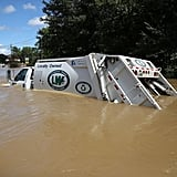 A swamped garbage truck illustrates just how high the waters are.