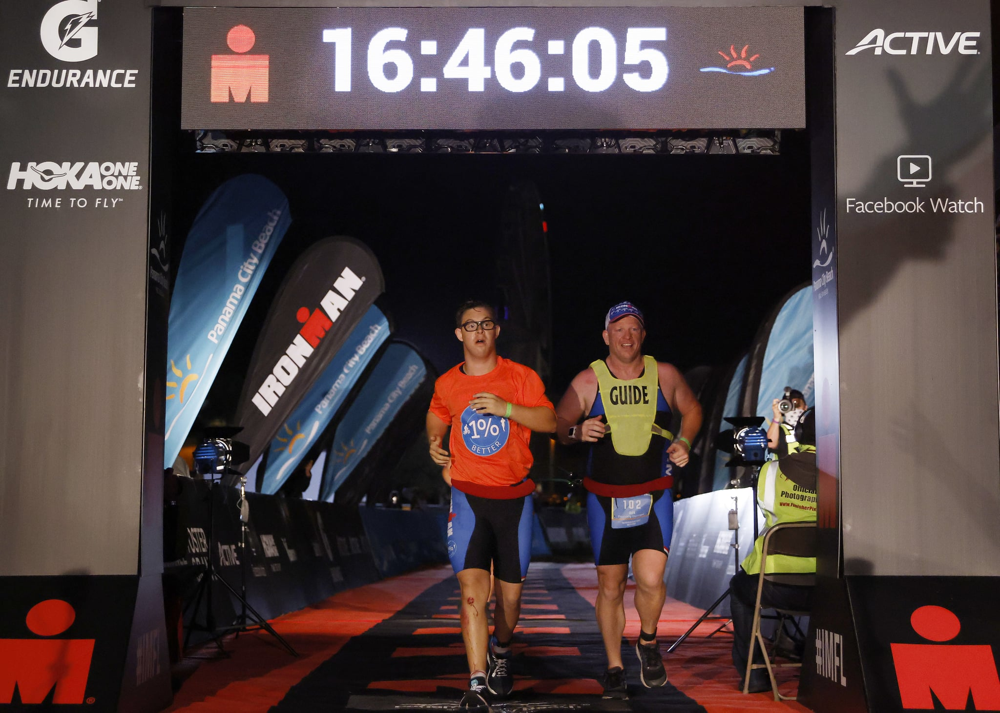 PANAMA CITY BEACH, FLORIDA - NOVEMBER 07: Chris Nikic and his guide Dan Grieb cross the finish line of IRONMAN Florida on November 07, 2020 in Panama City Beach, Florida. Chris Nikic became the first Ironman finisher with Down syndrome. (Photo by Michael Reaves/Getty Images for IRONMAN)