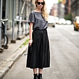 This is simple enough, but we love how a pleated midi skirt puts a sweeter spin on a basic blouse and boots.