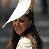 Kate Middleton smiles in her fascinator at the wedding.