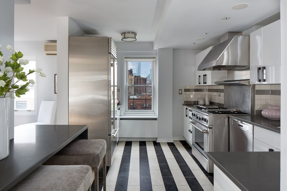 The striped floors in the galley kitchen complement the gleaming, stainless-steel appliances.