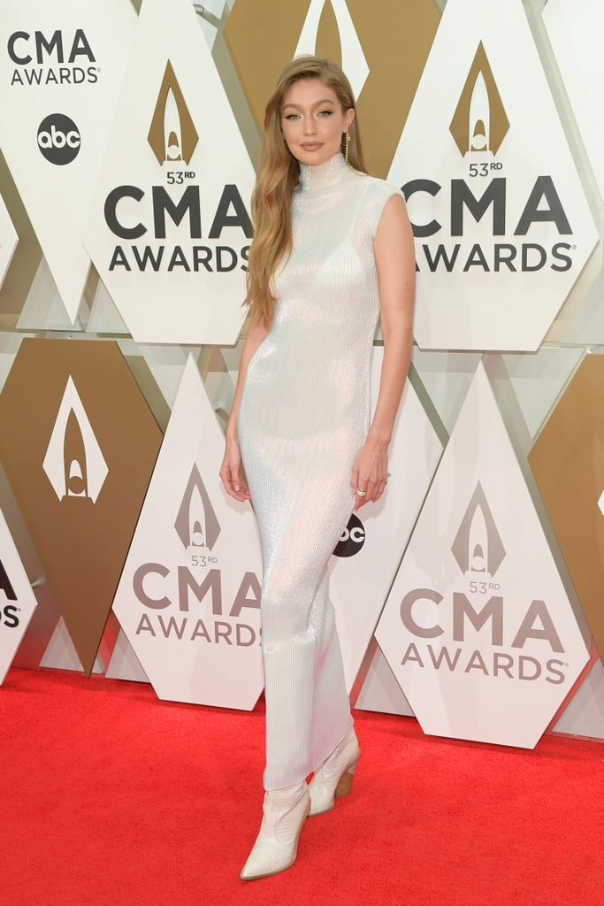 Gigi Hadid was among the glamorous attendees of the CMA Awards on Wednesday night, and she shimmered on the red carpet in a delicate pleated column dress by Helmut Lang. Gigi's slinky little number, from the brand's Spring 2020 collection, featured a high neck and long skirt, but though it was fairly covered up, it still managed to look sexy thanks to its sheer finish and figure-hugging shape. As the model posed on the red carpet, the dress glistened like mother of pearl, reflecting the light perfectly. Gigi finished her look by adding some unexpected footwear — a pair of chunky heeled, Western-inspired boots — before stacking up the gold jewelry, including yellow gold and diamond hoop earrings by Graziela Gems, drop earrings by Melinda Maria, an Established Trio ring with diamonds, and a Nouvel Heritage sapphire coral ring. Keep reading to take a closer look at the outfit from all angles.      Related:                                                                                                           Kacey Musgraves and Gigi Hadid Turned the CMA Awards Into a Glam Girls' Night Out