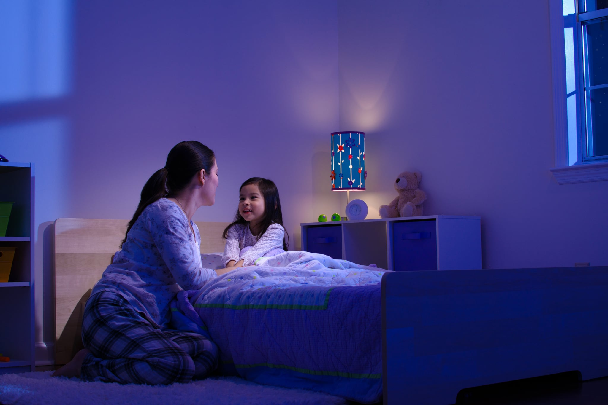 Mother talking with her child before bedtime, smiling.