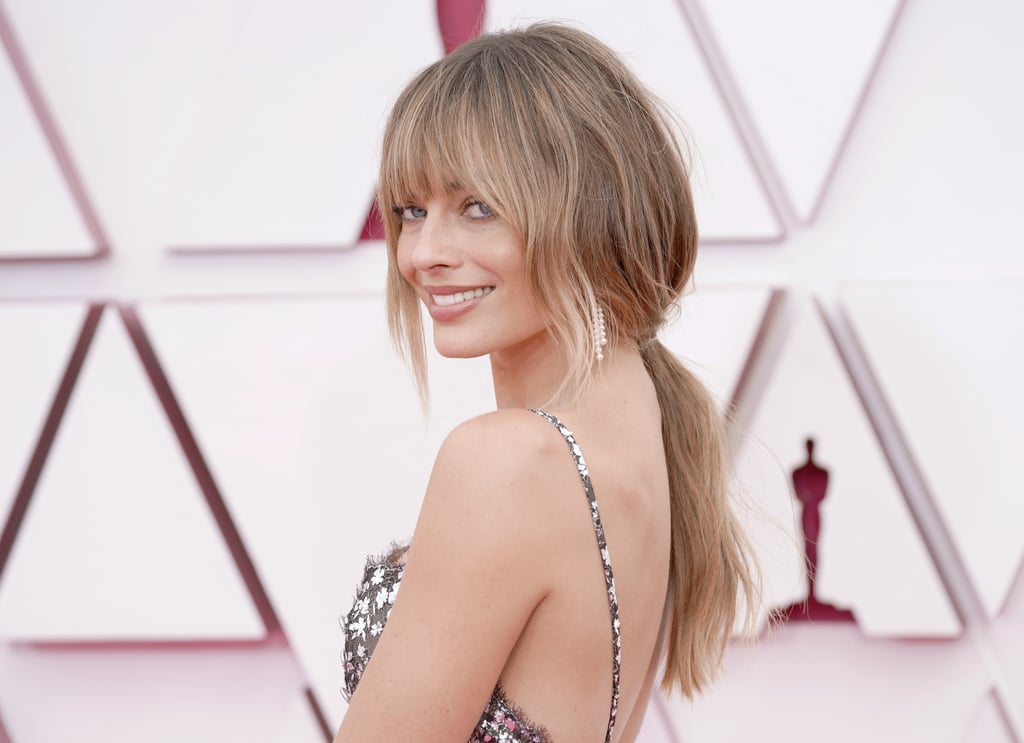 """As if Margot Robbie could get any more breathtaking, she debuted a new bangs haircut at Sunday's Oscars that had us doing a total double take. The Promising Young Woman producer arrived on the red carpet with darker blonde hair and wispy bangs, ditching her signature golden look. She wore her new style in a gorgeous low ponytail courtesy of celebrity hairstylist Bryce Scarlett, while her matching """"bronzey sunshine glow"""" was the work of makeup artist Pati Dubroff and Chanel Beauty. The details served as the perfect complement to the actress' dainty custom Chanel dress, rounding out Robbie's effortless look ahead."""