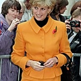 For a 1995 trip to Liverpool, Diana wore an orange Versace skirt suit with a black polo neck, belt, purse, and opaques.