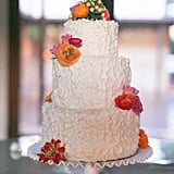 Small bunches of ranunculus, poppies, and dahlias offer color to this white-spackled wedding cake.