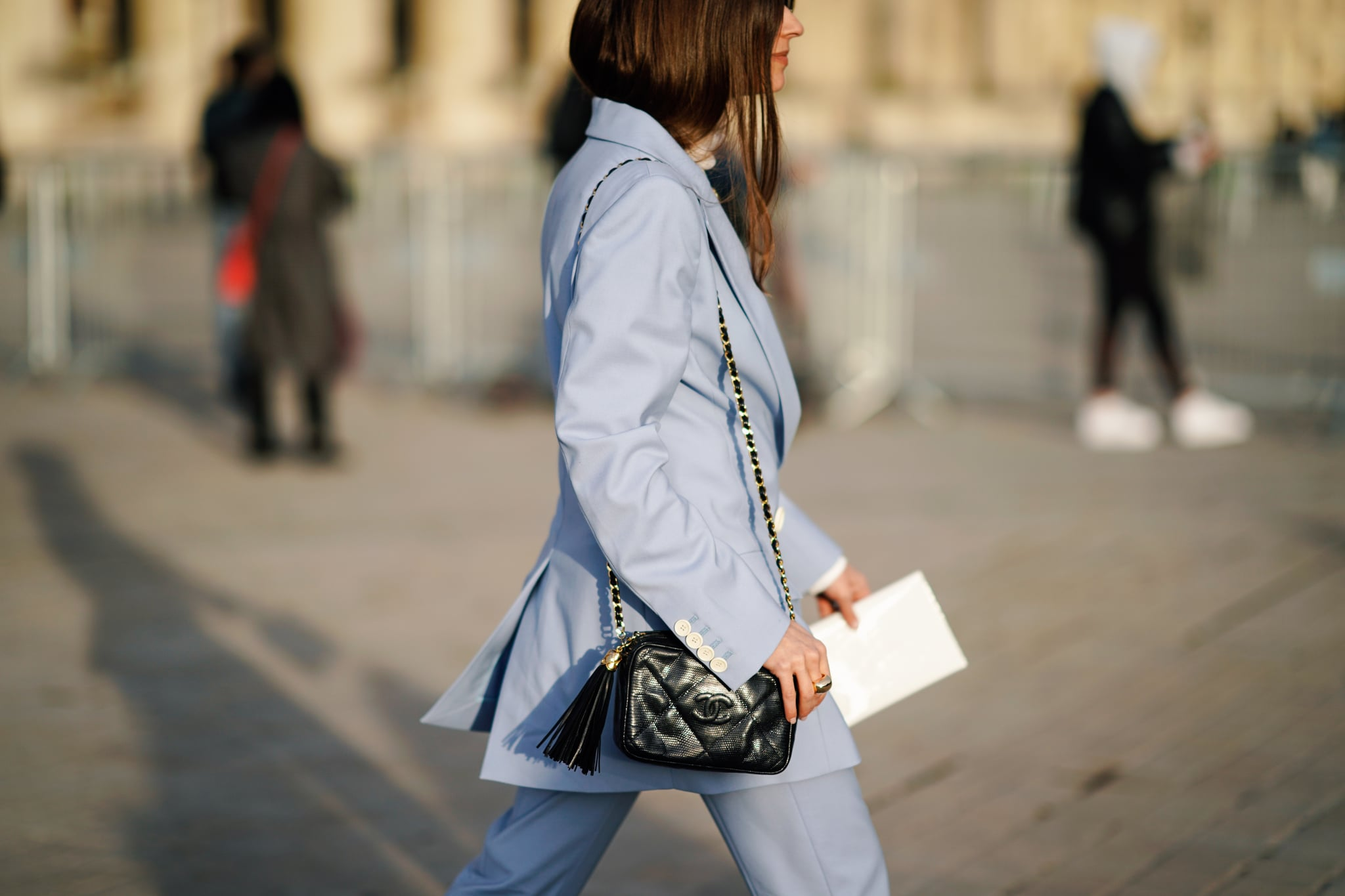 PARIS, FRANCE - MARCH 05: A guest wears a light blue pantsuit, a black Chanel bag with a pompon, outside Louis Vuitton, during Paris Fashion Week Womenswear Fall/Winter 2019/2020, on March 05, 2019 in Paris, France. (Photo by Edward Berthelot/Getty Images)