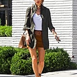 Dressed-up casual: white tee, green jacket, gold aviators, gold choker, lace-up heels, leather satchel