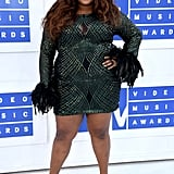 Even when she's not performing, Lizzo steals the show in outfits like this shimmery green dress with eye-catching feathered sleeves, which she wore to the 2016 MTV VMAs.