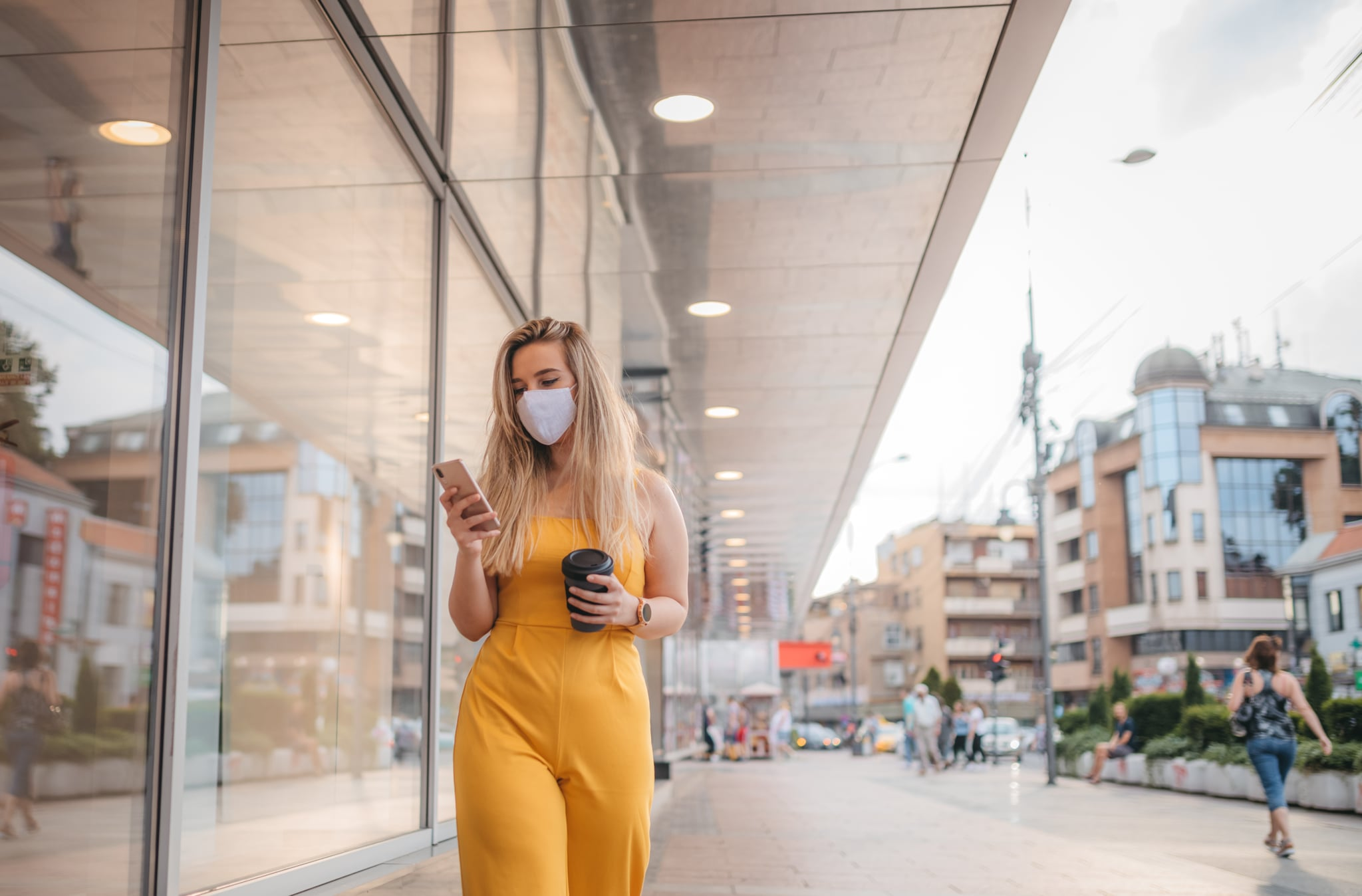 Woman wearing protective mask, using mobile phone