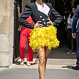 Playing with opposites, Celine paired this structured Ronald Van Der Kemp blazer with a whimsical marigold skirt. Note the mismatched Jimmy Choos.