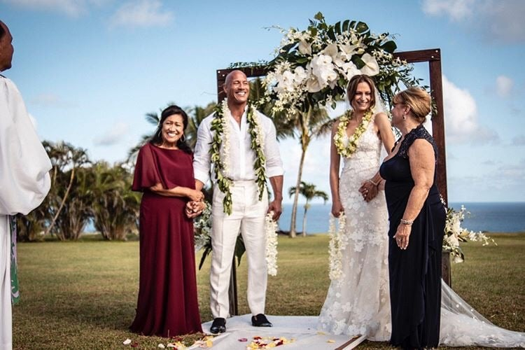 """Since tying the knot on Aug. 18, newlyweds Dwayne Johnson and Lauren Hashian have been sharing gorgeous snapshots from their ceremony on Instagram. The 47-year-old actor and 34-year-old singer said their vows in Hawaii — where they also took their honeymoon — in front of friends and family, including their daughters, 3-year-old Jasmine and 1-year-old Tiana. While Lauren stunned in a lace Mira Zwillinger gown, Dwayne looked sharp in a white button-up and tailored pants. On Aug. 31, Dwayne posted even more photos from the wedding reception, where he swapped threads, sporting a Hawaiian shirt and white bottoms. """"We love you family. On our wedding day, thank you for giving us your full hearts, love and support,"""" he captioned a gallery. """"Meant the world to us. Our ohana who sang beautiful songs and danced gorgeous hulas for us, also known in the streets as droppin' it like its hot."""" Other pictures — captured by photographer Dustin Shepard — show the two lovebirds embracing, gazing into each other's eyes, and posing alongside their mothers, Ata and Suzanne. Dwayne and Lauren first met in 2006 while the former wrestler was filming The Game Plan. They began dating the following year and welcomed Jasmine and Tiana in 2015 and 2018, respectively. Dwayne also shares daughter Simone with ex-wife Dany Garcia. By the looks of it, Dwayne and Lauren are ready to embrace their new lives as husband and wife. Look ahead to see some of the most beautiful pictures from their wedding!      Related:                                                                                                           Get a Rare Glimpse of Dwayne Johnson and Lauren Hashian's Love Story"""