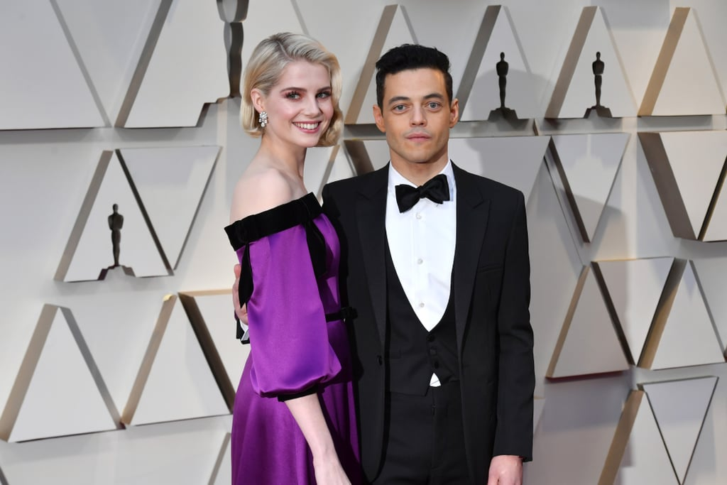 "Rami Malek and Lucy Boynton have been dating for a little over a year now after playing love interests in Bohemian Rhapsody. Aside from their cute award season appearances, the couple is usually pretty private when it comes to their romance. However, the 38-year-old actor recently gave us an inside look at their relationship while doing an interview for GQ's September issue. During the interview, Rami proved what a thoughtful boyfriend he is as he stopped to purchase a gift for his other half at Gwyneth Paltrow's Goop store in NYC.  Even though they weren't celebrating anything special, Rami picked up a container of Schmidt's Jasmine Tea deodorant. ""Actually, she wants deodorant. Does it have aluminum in it?"" he asked. ""She'll be so chuffed."" He also picked up a gold chain with a crescent-shaped pendant and asked if he should get a card before requesting that the salesperson place the deodorant in a jewelry box and put the necklace in a shopping bag as a joke. ""Good. This will be funny. She'll think I'm being goofy,"" he said.  The 25-year-old actress also briefly opened up to The Cut recently about what it was like meeting Rami for the first time at Abbey Road Studios in London before they started shooting together. ""Rami felt so much the leader of that set,"" she explained. ""The cast became so close going through that, as you always do when going through a particularly stressful experience, to put it politely."" Rami and Lucy have been together since April 2018, but it wasn't until this past January that they finally confirmed their romance at the Palm Springs International Film Festival."