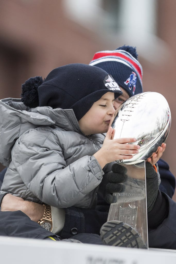The New England Patriots celebrated their Super Bowl XLIX victory with a parade through the streets of Boston, MA, on Wednesday. Quarterback Tom Brady brought his youngest son, Benjamin, along for the action, and the little guy even got to hold (and kiss!) the Lombardi Trophy while atop a float. The family fun comes after Tom first celebrated the win on the field with his wife, Gisele Bündchen, and sons, Jack and Ben, on Sunday after the big game. He also picked up the MVP honor, but his on-field antics were enough to have us awarding him the prize for cutest family as well. Congratulations to the whole Brady family and the Patriots!