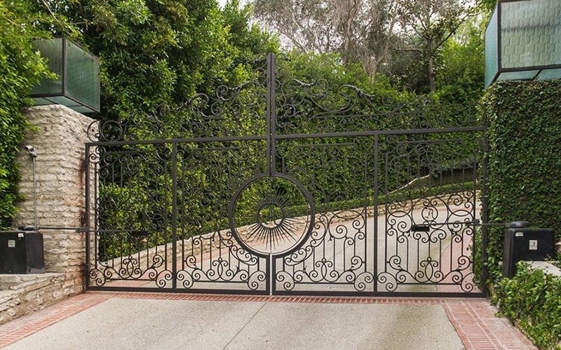 An intricate iron gate keeps strangers out of the Holmby Hills estate.