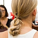 No hair tie? No problem. To re-create the look from the Creatures of Comfort runway show, simply begin by splitting your hair into two sections and twisting them around each other. Then, fold the twists up and tie the ends around the hair at the nape of your neck to keep the style in place.