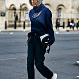 String a statement necklace around the collar of your sweater, and pair sharp white booties with thick trousers.