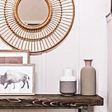 Thoughtful decor pieces like vases ($158 for set of five) and framed art in a neutral color palette transform the once-bare space into a gracious entryway. To help hold odds and ends, Monica scattered numerous baskets ($152 for set of three) and bowls ($29) throughout the space.