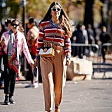 Temper a multicolored knit with camel pants and neutral accessories.