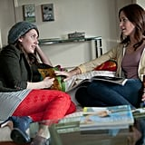 Alison Brie's character, Suzie, lounging in red printed leggings; Violet in a comfy hoodie with jeans.