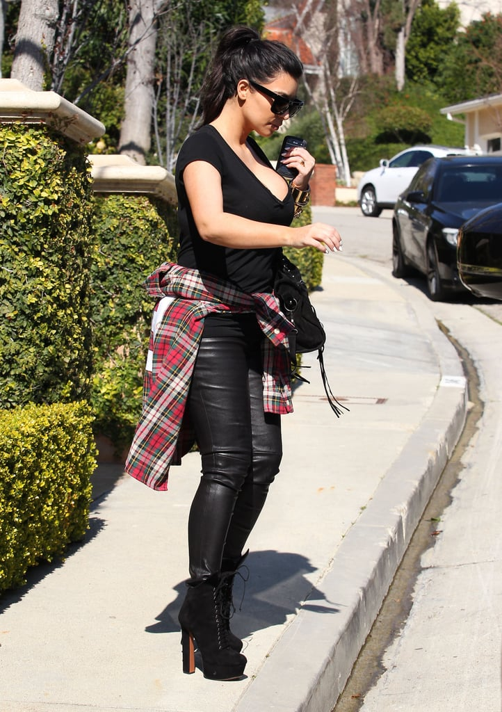 Kim Kardashian covered her baby bump with a flannel t-shirt tied around her waist.