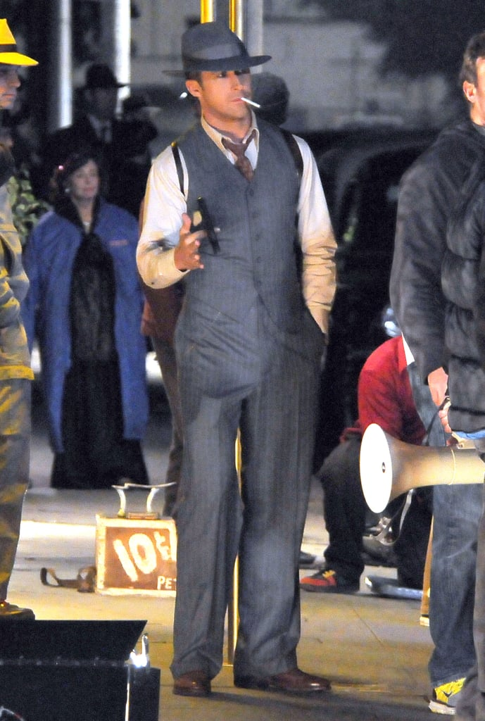 Ryan Gosling got into character on the LA set of his 1940's drama, Gangster Squad, last night. He modeled a well-tailored three-piece suit as well as a fedora. Ryan also carried a gun, though this time it was a pistol that was far smaller than the large prop shotgun he toted around earlier this week.  The actor is keeping busy on set while, around the globe, his girlfriend Eva Mendes is filming her own project, Holly Motors. The pair sparked up a romance shooting The Place Beyond the Pines over the Summer and have been going strong ever since. A busy schedule hasn't kept Ryan from seeing Eva. Ryan and Eva reunited in France over Thanksgiving and were seen holding hands on a romantic evening stroll through the City of Lights.