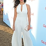 Wearing a pleated flare jumpsuit with a cutout neckline and a gold clutch.