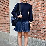 With girlie pleats and heels.