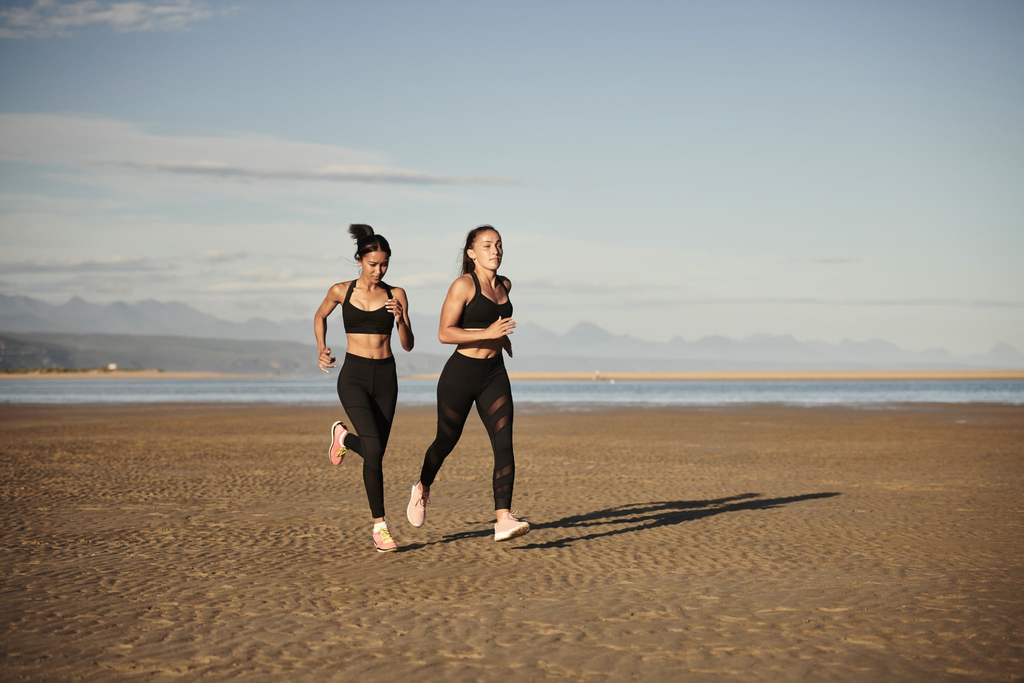 2 female runners on beach wearing black outfits