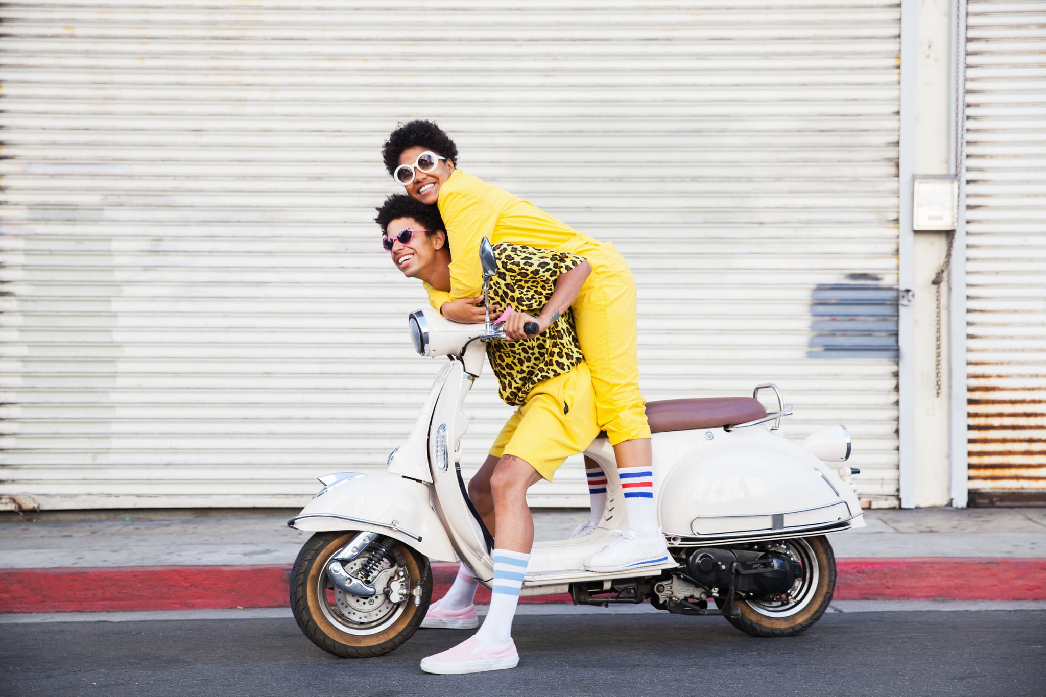 A hip young African American couple wearing bright yellow outfits posing on a scooter on a city street