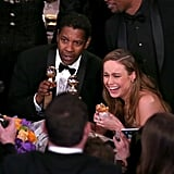 Denzel Washington cracked up with Brie Larson, who was eating a burger.
