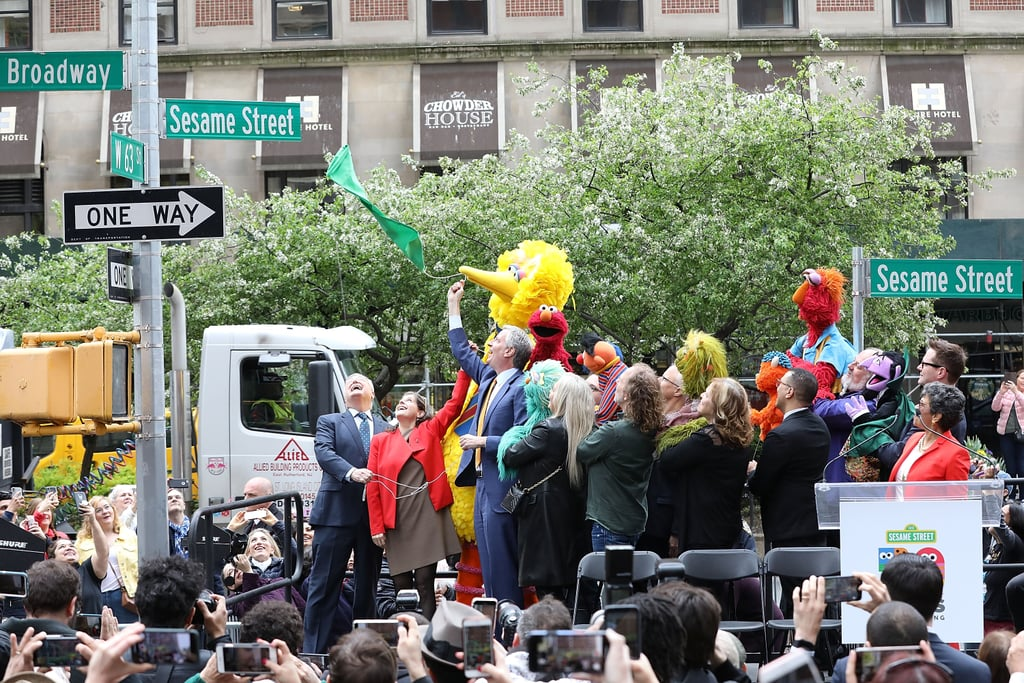 """As a kid, I used to ask my mom how to get to Sesame Street every time the show's theme song played with its iconic """"Can you tell me how to get, how to get to Sesame Street?"""" line. Now, parents can give their kids a definitive answer to that question, as Sesame Street is a very real street in New York City in honor of the show's 50th anniversary — and yes, it's permanent! In celebration of the new """"Sesame Street Day"""" on May 1, Mayor Bill de Blasio, Big Bird, Cookie Monster, Elmo, Ernie, and the rest of the crew took to the corner of Broadway and 63rd St., dubbing the intersection Sesame Street, green sign and all.      Related:                                                                                                           Kids Weigh In on That Viral Sesame Street Clip, and Their Reactions Will Make You Giggle               """"Fifty years of extraordinary programming, 50 years of making people's lives better, 50 years of helping children believe in themselves,"""" Mayor de Blasio said on Wednesday. """"There is also something beautiful for us watching when they were young to see our own city, even our own neighborhood portrayed in Sesame Street. And you cannot take the New York City out of Sesame Street, can you?"""" No you most definitely cannot! See some of the photos from the sweet day ahead (and pick up some 2019 Sesame Street stamps the next time you're out!).      Related:                                                                                                                                Elmo Just Taught Cersei and Tyrion a Thing or 2 About Respect, and We're LOL-ing All the Way to Westeros"""
