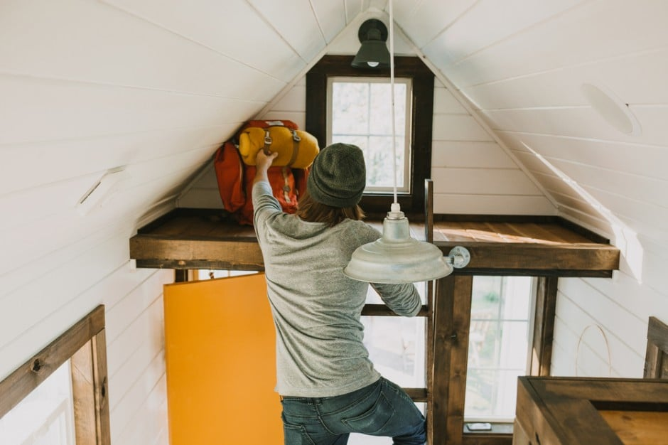 A triangular nook near the ceiling includes a ladder bar for easy access to storage.