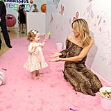 "Heidi Klum played with a little girl at the launch of her Babies""R""Us Truly Scrumptious collection in NYC."
