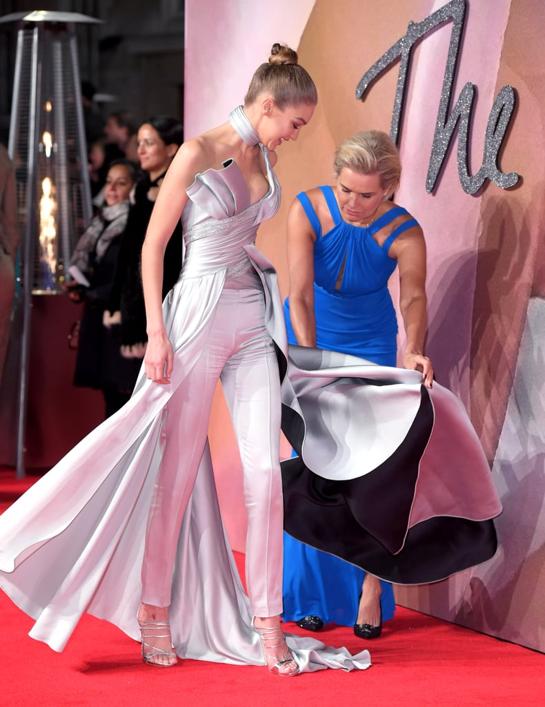 A week after slaying the Victoria's Secret Fashion Show runway, Gigi Hadid took home model of the year at the British Fashion Awards on Monday. The blonde bombshell — dressed in a stunning, silver Atelier Versace two-piece dress and pants set — brought mom Yolanda along to help her celebrate the honor, where the two giggled on the red carpet and flashed matching smiles for photographers. Yolanda, in full-on, adorable mom mode, even fussed with Gigi's dress on the carpet, ensuring her gorgeous daughter had a perfect night. No wonder both Gigi and sister Bella love turning every event into a family affair!
