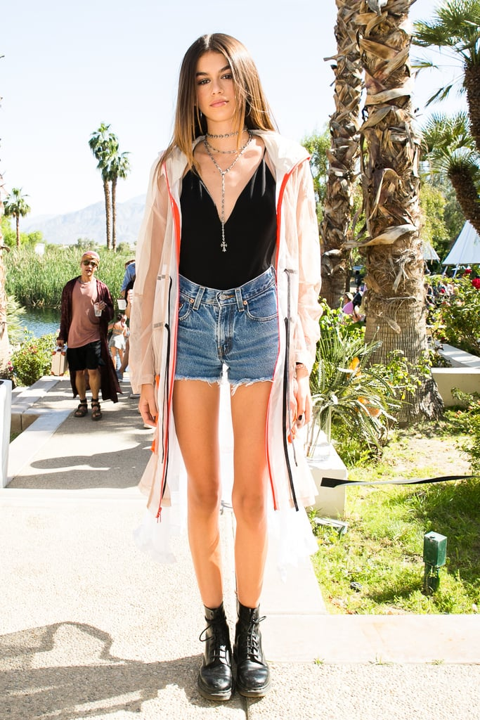 Kaia Gerber wearing a black bodysuit, denim shorts, black boots, and DKNY jacket at the Revolve Festival party.