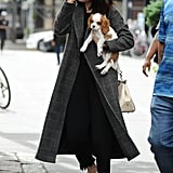 Wearing a menswear-inspired coat, white sneakers, frayed black jeans, her Selena Grace Coach bag and black sunglasses..