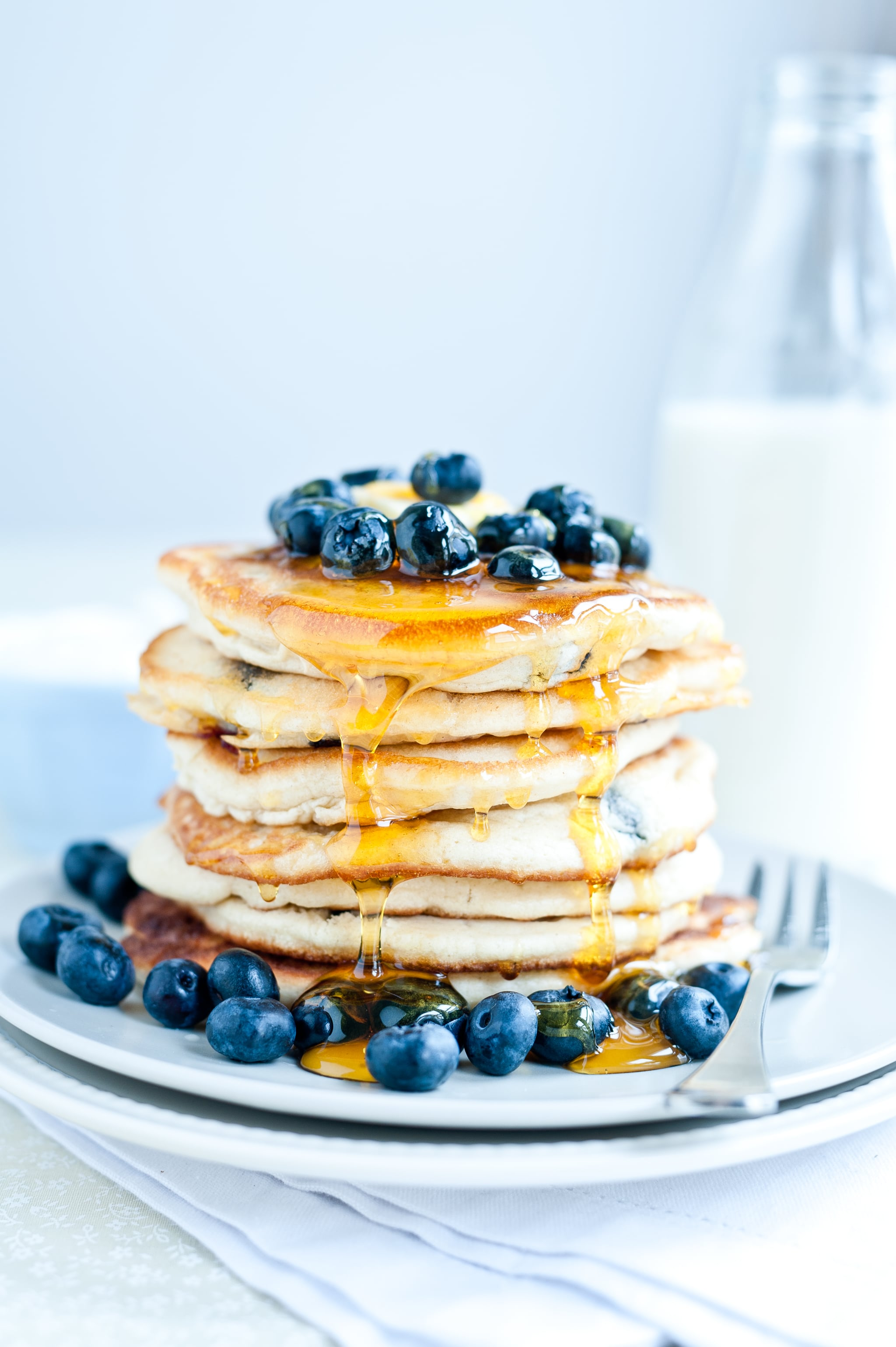 Blueberry pancakes with fresh blueberries and golden syrup.