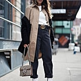 Tuck a white sweater into a pair of high-waisted jeans. Complete your casual Fall look with a beige trench coat.