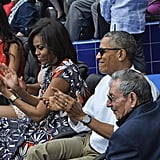 Michelle wearing a bright floral Tory Burch dress at a baseball game in Havana.