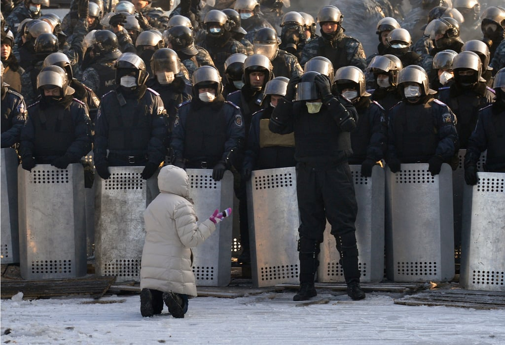A woman spoke out as she knelt in front of police in Kiev.