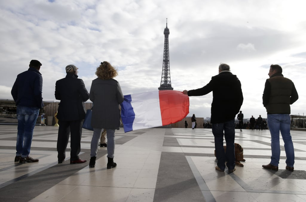Paris was rocked by terrorist attacks that killed at least 129 people on Friday night, and in the wake of the tragic events, people all over the world are honoring the victims. France officially observed three days of national mourning and on Monday fell quiet for a minute of silence to remember the lives lost. Monuments around the world, including London's Tower Bridge, were lit up in France's blue, white, and red while sports events stopped in tribute to Paris. Read on for the heartwarming and touching photos that show people from around the world honoring Paris and then find out how you can donate to the victims.