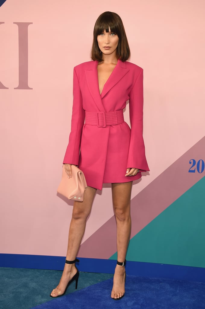 While Gigi Hadid went the minimalist route at the 2017 CFDA Awards in The Row, sister Bella chose a statement dress for the red carpet. The magenta number by Off-White featured structured padded shoulders and a retro-style wide belt that cinched in the model's waist. The bold look was very '80s, and Bella even changed up her hair with bangs and a blunt cut. Scroll on to see her blazer-like minidress.