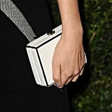 Her sleek white Chanel box clutch offset the cool crisscross print of her minidress.