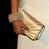 Freida's gold clutch and pearl bracelet.