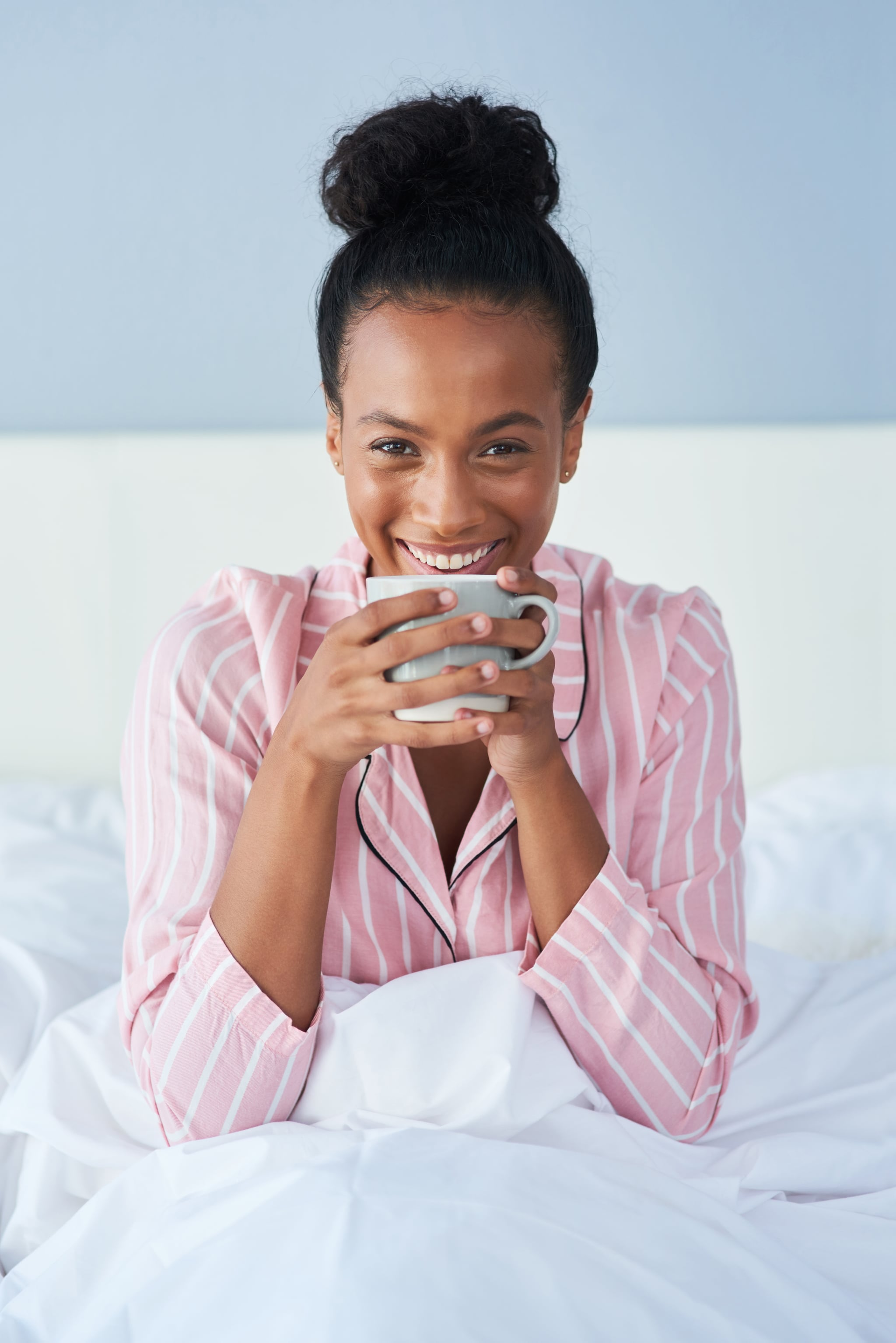 Shot of an attractive young woman enjoying her morning coffee in bed at home
