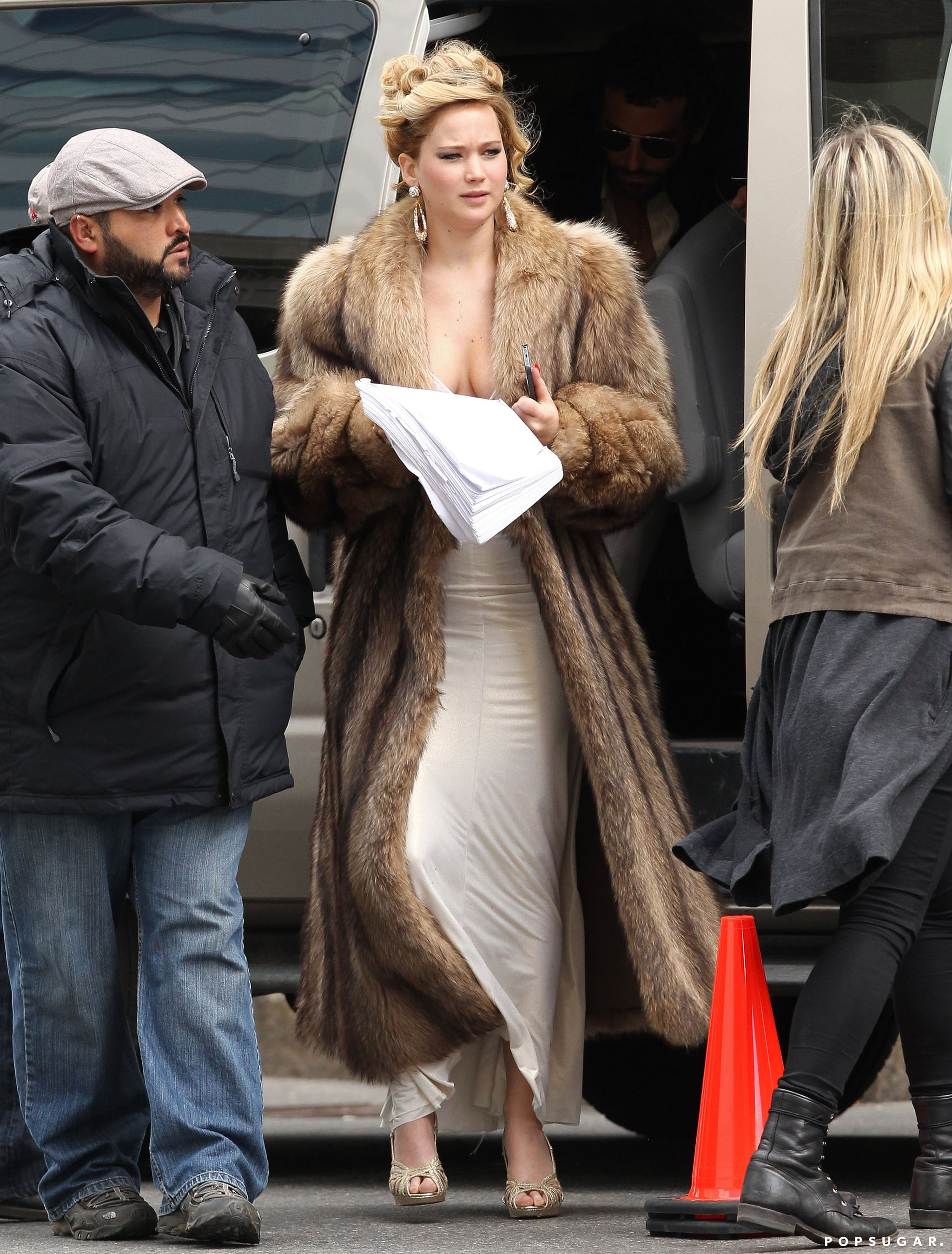 Jennifer Lawrence hid her cleavage under a fur jacket on set in Boston.